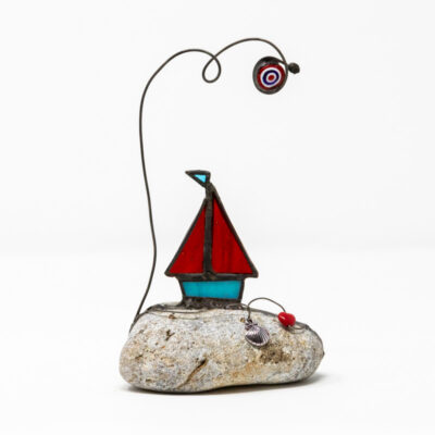 Sailing boat on rock red sails