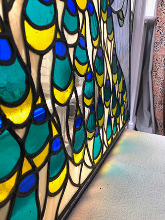 Repaired stained glass peacock panel